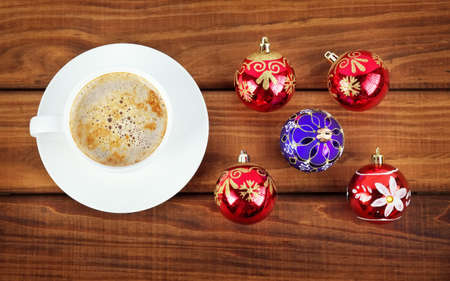 christmas bubbles: Cup of coffee and christmas bubbles on wooden background.