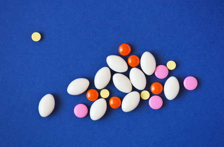 antibiotic pink pill: Medicine pills on blue background. Drug prescription for treatment medication. Pharmaceutical medicament for health. Antibiotic, painkiller closeup.