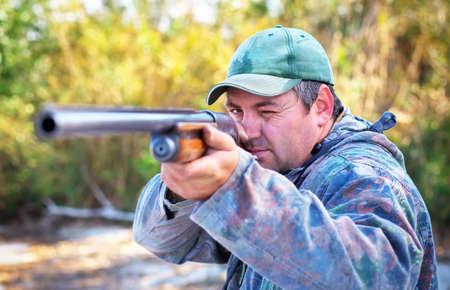 cazador: Hunter apuntando a la diana. Cazador con un arma de fuego.