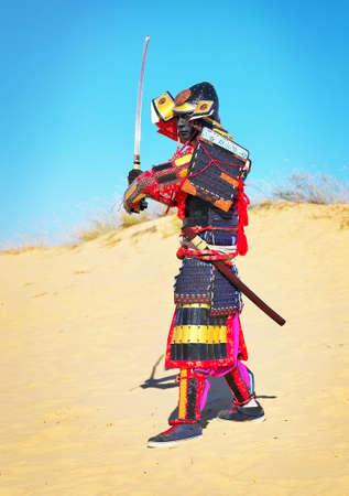 samurai sword: Man in samurai costume with sword running on the sand. Men in samurai armour running on the sand. Original Character Stock Photo