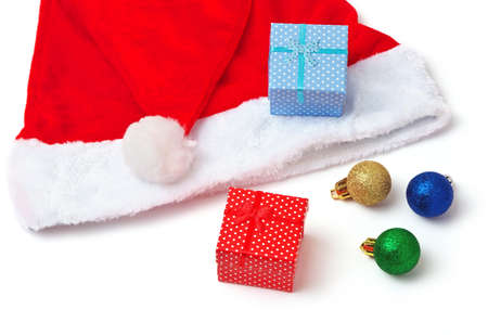 greem: Santa Claus red and white hat, toy bubbles and christmas gifts on white background. Stock Photo
