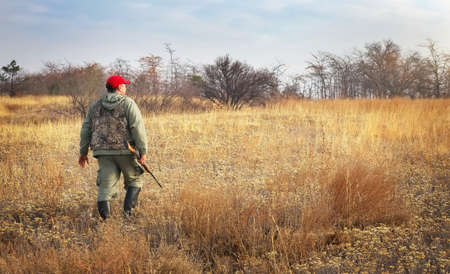 woods: Hunter moving with shotgun looking for prey. Hunter with a gun. Hunting for hare Stock Photo