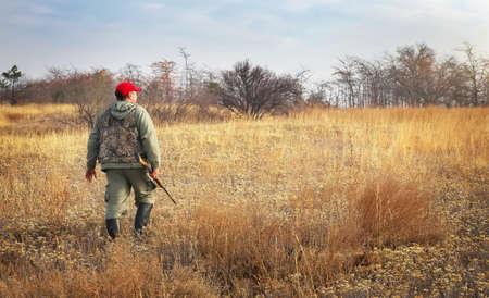 cazador: Hunter se mueve con la escopeta en busca de presas. Cazador con un arma de fuego. A la caza de la liebre