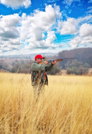 hunter: Hunter with a gun. Hunter taking aim at the target. Hunting for hare