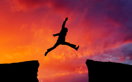 cliff jumping: Man jumping across the gap from one rock to cling to the other. Man jumping over rocks with gap on sunset fiery background. Element of design.