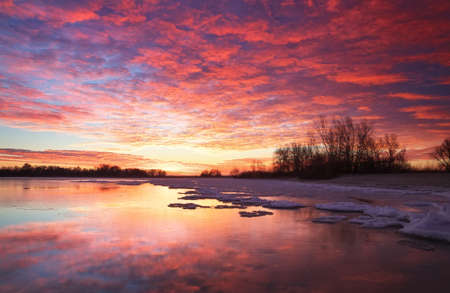 lake sunset: Beautiful colorful winter landscape with frozen lake and sunset sky. Unusual weather phenomenon