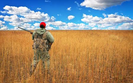 cazador: Hunter se mueve con la escopeta en busca de presas en el campo. Cazador con un arma de fuego. A la caza de la liebre