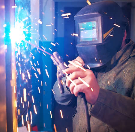 prefabricate: Worker with protective mask welding metal and sparks