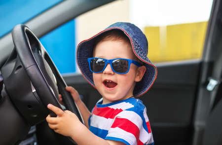 mesmerized: Happy cute little boy with glasses sitting in the car and keeps the wheel