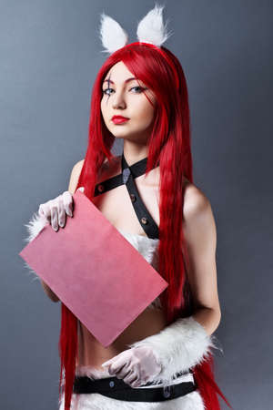 Beauty Fashion Model Girl with red wig on gray background, holding a sheet of paper.