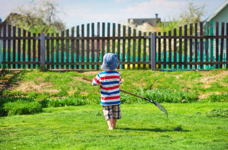 A little boy of about two years old, working in the garden.