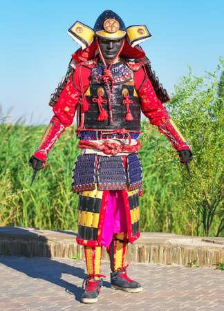 Der Mensch in der Samurai-Kostüm mit einer scharfen tödliche Waffe in den Händen.