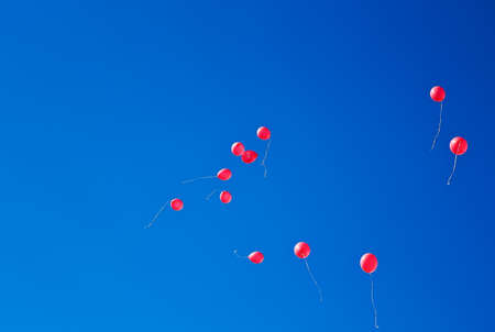 Red balloons flying on the blue sky