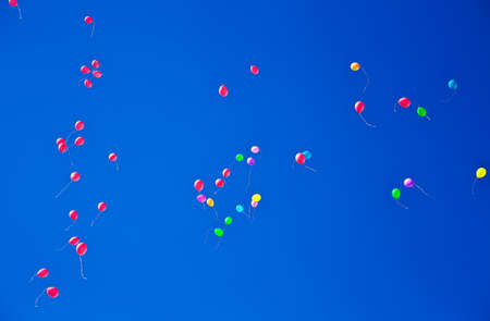 Lots of colorful balloons flying on blue sky