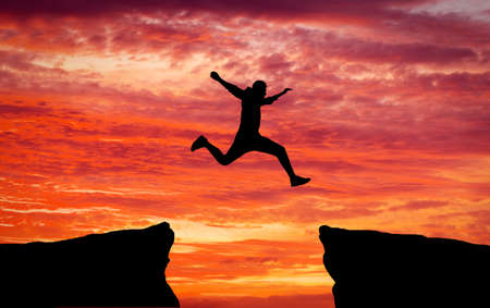 Man jumping across the gap from one rock to cling to the other. Man jumping over rocks with gap on sunset fiery background. Element of design. Imagens - 64601660