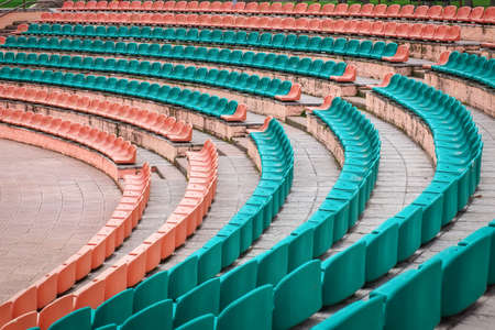 arena: Empty old plastic seats at stadium, open door sports arena. Stock Photo