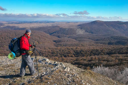 Photographer takes pictures on top of the mountain in autumn. Traveler with backpack on mountain top