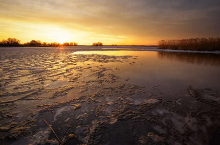 reflaction: Winter landscape with river, reeds and sunset sky. Composition of nature.