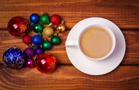 christmas bubbles: Cup of coffee and different christmas bubbles on wooden background.