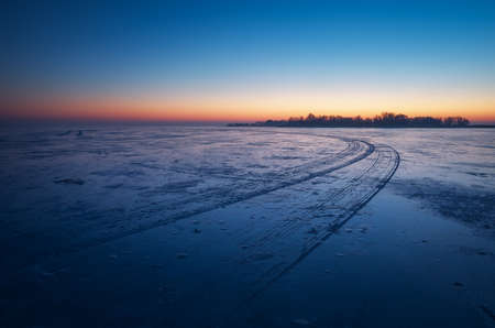 Trails on the surface of frozen lake. Winter Landscape with trails on frozen lake and sunset fiery sky.   Stock Photo