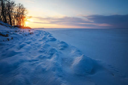 Beautiful winter landscape with sunset sky and frozen lake
