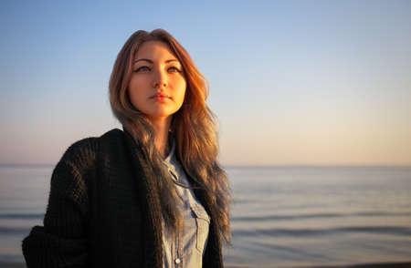 サンライズの中に海のそばの秋の美しい少女の屋外ポートレート