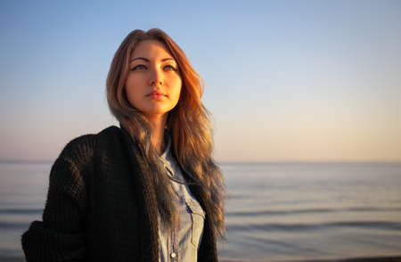 Outdoors portrait of young beautiful girl in autumn near the sea during sunrise