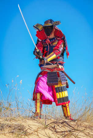 Samurai mit Schwert auf dem Sand. Männer in Samurai-Rüstung auf dem Sand. Original-Charakter