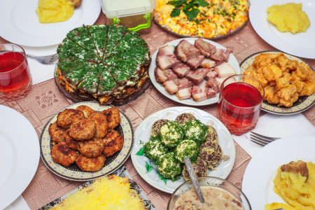 ensaladilla rusa: Festive dinner at home, Christmas Day. Bacon, cheese balls, fried fish in batter, cutlets, mushed potato, liver cake, fruit compote in a glass and other.