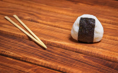 ball lump: Japanese onigiri with chopsticks on wooden background. Rice ball with filling, wrapped seaweed nori