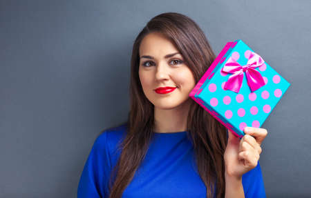 Beautiful girl holding gift box on gray background Stock Photo