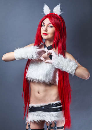 Beauty Fashion Model Girl with red wig on gray background. Cosplay Character from game