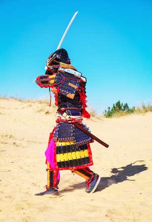 Männer in Samurai-Rüstung mit Schwert auf Sand läuft Standard-Bild