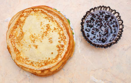 Pancakes with raspberry jam on the table. Maslenitsa Festival