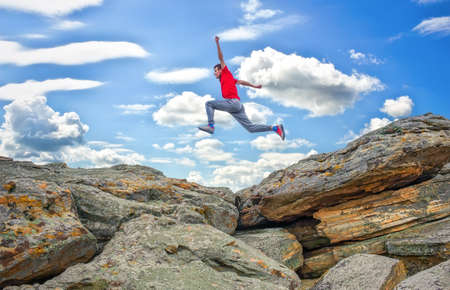 Sportsman running, jumping over rocks in mountain area. Training running and jumping in difficult conditions in a beautiful nature with cloudy sky