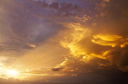 Beautiful dark fluffy cloudy sky with sun rays. Sunset light.  Stock Photo