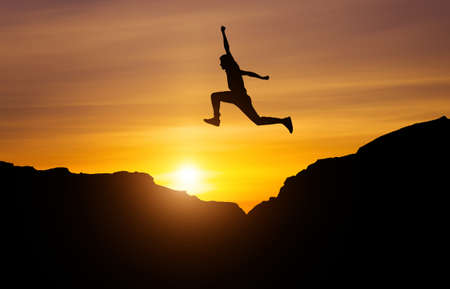Silhouette of athlete, jumping over rocks in mountain area against sunset. Training running and jumping in difficult conditions in a beautiful nature with cloudy sky