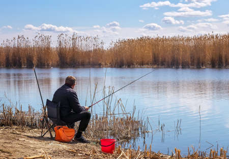 A fisherman with a fishing rod sitting on a chair on the river bank. The concept of a rural getaway.  Stock Photo