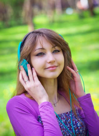Beautiful young girl with headphones at the park