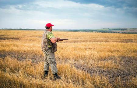 Łowca porusza się z shotgun patrząc na zdobycz.