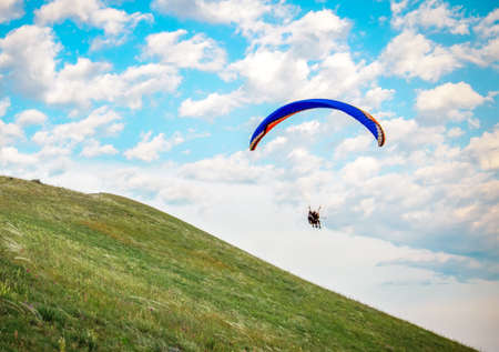 Trike with a parachute against the blue sky. Paragliding flying over the clouds Stock Photo