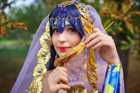 Beautiful girl in original suit, cosplay character in autumn park. Anime festival