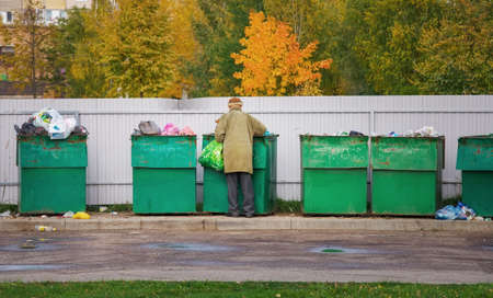 Poor homeless old man searching in garbage in autumn time. Men rummaging in trash container looking for food and reusable goods Imagens - 92334064
