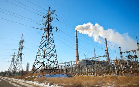 High voltage power lines in the winter. Thermal power plant. High-voltage transformer substation. Stock Photo