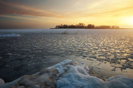 Beautiful winter landscape with frozen lake and sunset sky. Composition of nature. Stock Photo