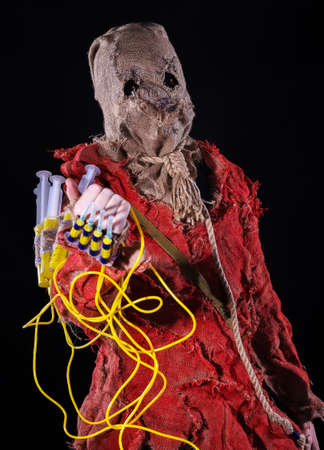 Scary Scarecrow character in a sackcloth suit with syringes on dark background. Cosplay hero Stock Photo