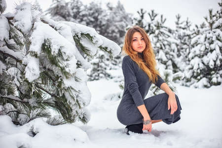 Pretty young girl posing in the winter in cold forest with pine trees.