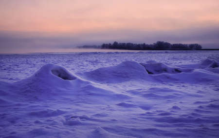 Beautiful winter landscape. Frozen river covered with snow. Sunset in ices. Ice hummocks