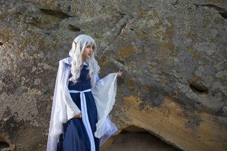 Beautiful Girl In an elf costume near the rocks Stock Photo
