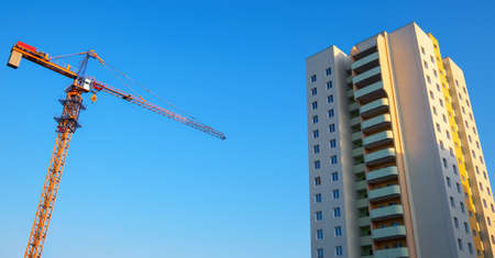 New high-rise building, crane and blue sky.